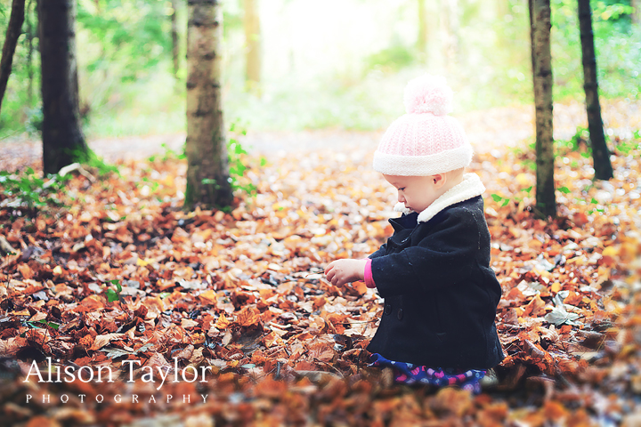 photo of a a little girl looking at leaves in the woods during a family photo shoot in Bristol