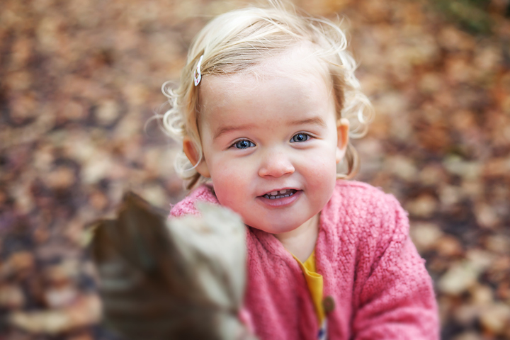 photo of a girl holding a leaf in the woods during a family photo shoot in Bristol