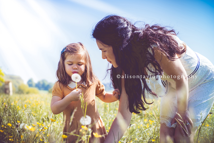 photo of a girl blowing a dandelion during a family photo shoot in Bristol