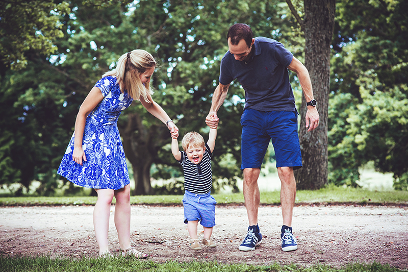 Photo of a boy holding parents' hands during a family photo shoot in bristol