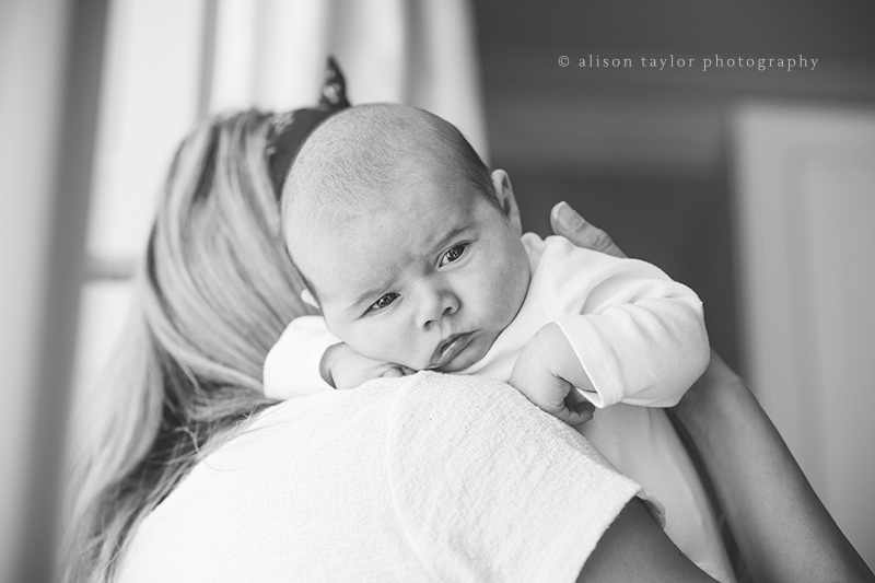 baby looking over mother's shoulder during a newborn baby photo shoot in Bath by Alison Taylor Photography
