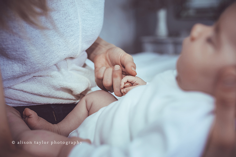 baby holding mother's finger during a newborn baby photo shoot in Bath