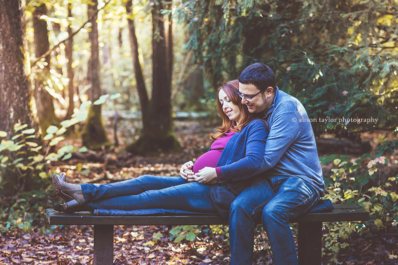 photo of a couple lying down on bench with baby bump at Leigh Woods in Bristol