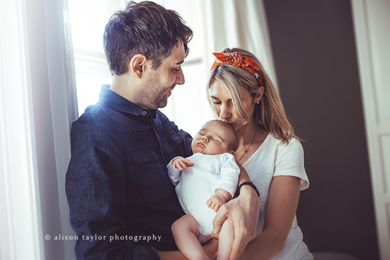 mother and father holding newborn baby - newborn photographer bath