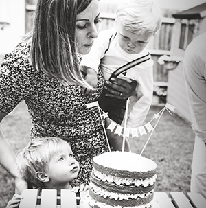 birthday party photography - mother with son blowing candles out
