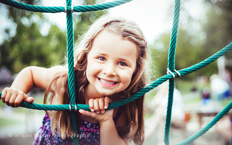 Portrait of a girl playing in the park - family photographer cheltenham