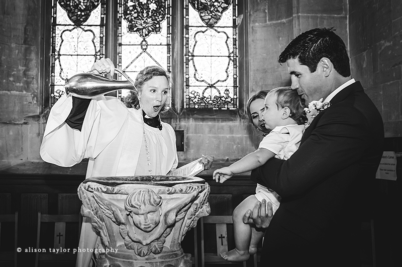 priest pouring water into font for christening